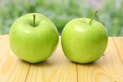 在木桌上的绿色苹果有绿色背景 图库摄影