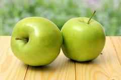 在木桌上的绿色苹果有绿色背景 免版税库存照片
