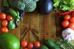 在木桌上美妙地是蔬菜和水果:蕃茄,黄瓜,鲕梨,茄子,硬花甘蓝,麝香草,蓬蒿,热的p 免版税图库摄影