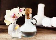 在木桌上设置的温泉 黄色兰花和淡紫色浴泡沫 库存图片