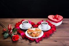 在木桌上,在玫瑰花瓣里面的心脏是两杯咖啡和一块板材用饼干 外面,玫瑰花 库存照片