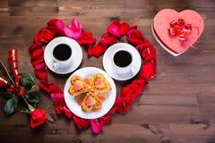 在木桌上,在玫瑰花瓣里面的心脏是两杯咖啡和一块板材用饼干 外面,玫瑰花 免版税图库摄影