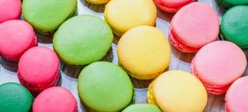 在木桌与花,法国甜纤巧,蛋白杏仁饼干纹理上的五颜六色的鲜美蛋白杏仁饼干 免版税库存照片