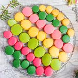 在木桌与花,法国甜纤巧,蛋白杏仁饼干纹理上的五颜六色的鲜美蛋白杏仁饼干 库存图片
