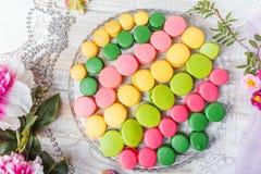 在木桌与花,法国甜纤巧,蛋白杏仁饼干纹理上的五颜六色的鲜美蛋白杏仁饼干 顶视图 免版税图库摄影