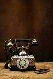 在木桌和一个手机上的葡萄酒电话 库存照片