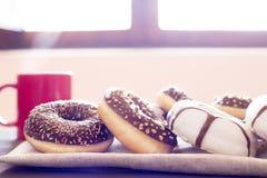 在木桌和一个红色杯子上的不同的油炸圈饼热的咖啡机智 免版税库存图片