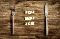在木桌和叉子设置的刀子,标志说上吃 图库摄影