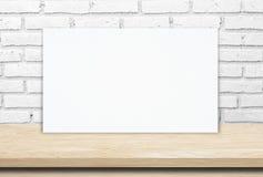 在木桌和砖墙背景的空白的白皮书海报 库存图片
