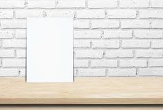 在木桌和砖墙背景的空白的白皮书海报 免版税库存图片