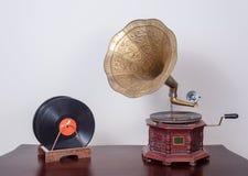 在木桌和米黄墙壁上的19世纪留声机留声机和唱片 库存图片