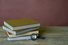 在木桌和红葡萄酒背景上的四本邮票册书束、放大器和镊子 免版税库存照片
