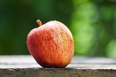 在木桌和自然绿色背景的新鲜的红色苹果 免版税库存照片
