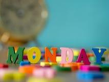 在木桌和葡萄酒闹钟上的五颜六色的木词星期一 库存照片