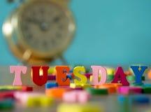 在木桌和葡萄酒闹钟上的五颜六色的木词星期二 免版税库存照片