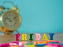 在木桌和葡萄酒闹钟上的五颜六色的木词星期五 免版税图库摄影
