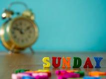 在木桌和葡萄酒闹钟上的五颜六色的木词星期天 免版税图库摄影