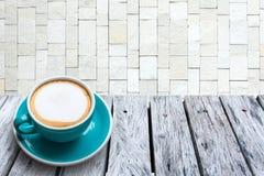在木桌和被堆积的石墙背景上的热奶咖啡 免版税库存图片