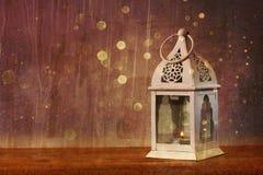 在木桌和闪烁的白色灯笼点燃背景 免版税库存照片