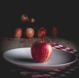 在木桌和黑背景上的一个有机苹果 库存图片