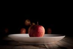 在木桌和黑背景上的一个有机苹果 免版税库存图片