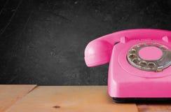 在木桌和黑板背景的减速火箭的桃红色电话 库存图片