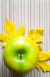在木桌和绿色苹果计算机黄色叶子背景  免版税库存照片