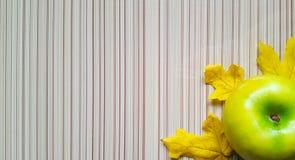 在木桌和绿色苹果计算机黄色叶子-秋天构成背景  图库摄影