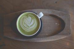 在木桌咖啡馆商店的热的绿茶拿铁艺术 库存照片