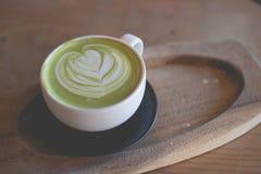 在木桌咖啡馆商店的热的绿茶拿铁艺术 免版税库存图片