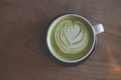 在木桌咖啡馆商店的热的绿茶拿铁艺术 免版税图库摄影