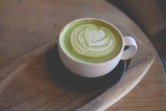 在木桌咖啡馆商店的热的绿茶拿铁艺术 库存图片