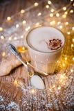在木桌圣诞节的乳脂状的姜咖啡 免版税库存图片