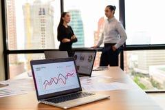 在木桌展示图和图表,分析事务的膝上型计算机财政和销售报告 免版税库存照片