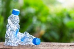 在木桌或柜台上的清楚的空的塑料瓶与绿色 库存照片