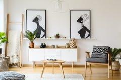 在木桌旁边的扶手椅子在明亮的客厅内部机智 免版税库存照片