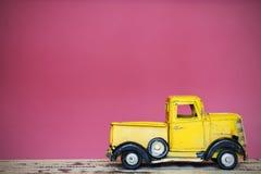 在木桌桃红色墙壁背景的微型黄色玩具汽车 库存照片