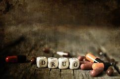 在木桌概念上瘾者的老破旧的污浊的照片药物药片 免版税图库摄影