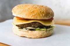 在木桌灰色背景的经典汉堡 免版税库存图片