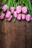 在木桌的桃红色郁金香 库存照片