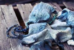 在木桌的蓝色紫色羊毛围巾纹理 免版税库存照片