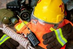在木桌背景安置的消防队员成套装备 免版税库存照片