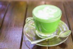 在木桌背景安置的玻璃的绿茶 免版税库存图片