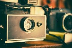 在木桌背景的减速火箭的照相机 35mm照相机slr葡萄酒 影片来了 免版税库存照片