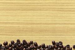 在木桌背景的咖啡豆 免版税库存照片