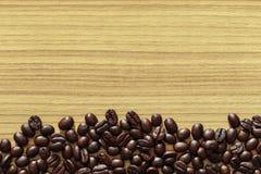 在木桌背景的咖啡豆 库存图片
