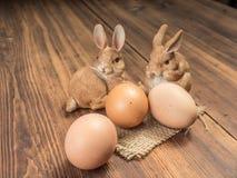 在木桌背景的复活节兔子从老委员会的有粗麻布和棕色鸡鸡蛋的 免版税库存照片