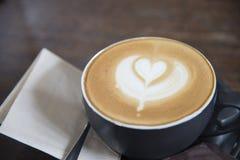 在木桌背景的拿铁艺术心脏形状咖啡顶视图 免版税库存照片