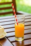 在木桌背景的橙汁 在户外绿色背景的汁液 库存图片