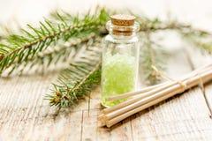 在木桌背景的瓶海芳香疗法的盐和冷杉分支和温泉 免版税库存图片